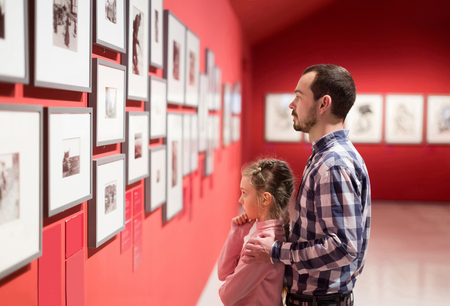 man and daughter at an art exhibit looking at prices